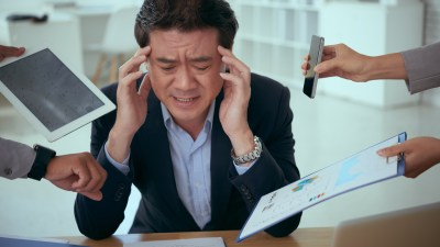 Businessman feeling overwhelmed as employees shove papers and phones in his face