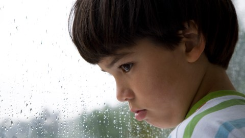 A child with ADHD looks sadly out the window after being disciplined by his parents.