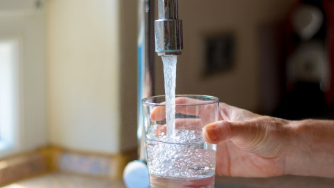 A parent of a child with ADHD has a glass of water to calm down and avoid disciplining too harshly.