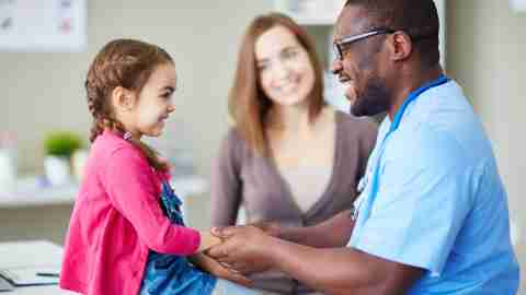 A doctor examines a child before school starts, a key part of your back-to-school list.