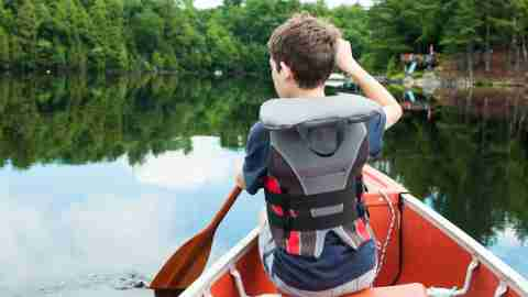 A young boy with ADHD canoeing at summer camp