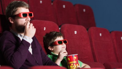 Father and son at a summer movie, enjoying their empty schedule