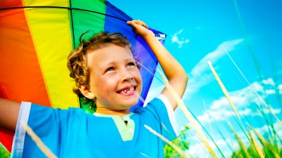 A smiling boy playing with a kite during the summer to prevent learning loss