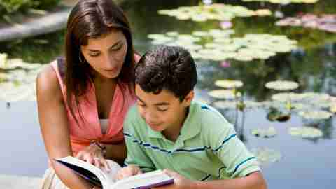 A boy and his mother reading a book during the summer to avoid learning loss