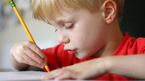 A child writing in a notebook with larger than usual spaces, a good school organization idea that helps adhd children.