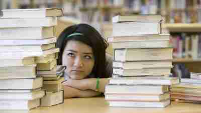 Highschool student with ADHD in library staring at stack of books preparing for college