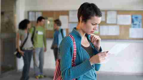 Teen with ADHD looking at paper in high school hallway