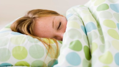 ADHD and sleep advice for adults like this woman sleeping on her side in bed.