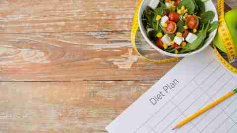 Bowl of salad with measuring tape and apple on table next to diet plan belonging to person with ADHD