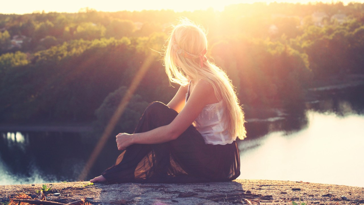 Woman with ADHD sitting on top of mountain overlooking lake at sunset thinking about her diagnosis