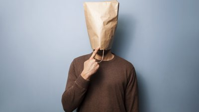 "A man with a bag over his head, wondering ""Why do I say stupid things?"""