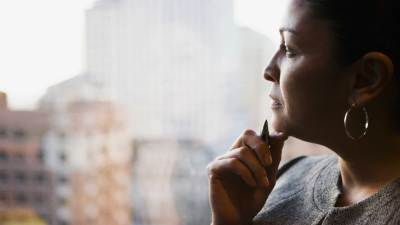 An executive with ADHD stares out a window at work