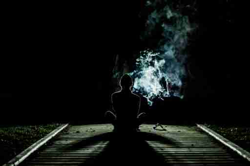 A teen sitting on the track, smoking