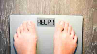 Someone with ADHD standing on a scale to track their weight loss