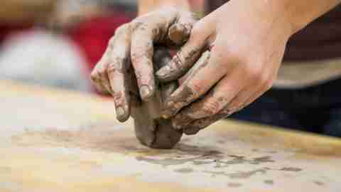 Hands of ADHD child molding clay on wooden table