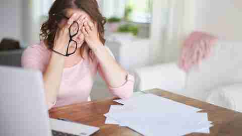 Stressed woman with ADHD holds head in hands over paperwork and bills