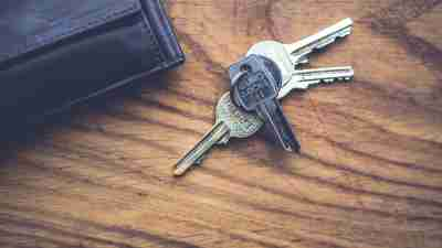 Set of keys by wallet on table in home of ADHD person trying to organize