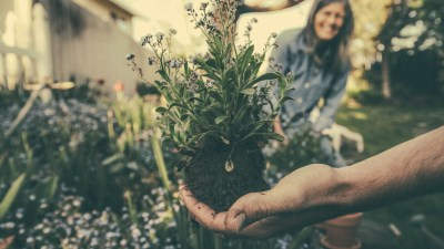 Man with ADHD holding plant up while gardening with woman smiling