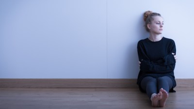 Girl with ADHD and depression sitting on floor by wall