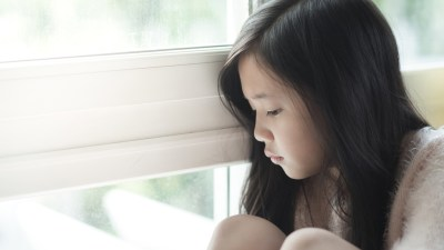 Girl with ADHD and depression sitting by window in home frowning