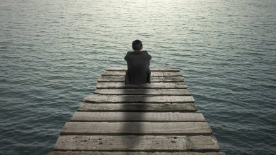 A man sitting on the edge of a dock, thinking about how his anxiety feels while he stares at the water