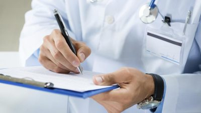 Doctor filling out a form to diagnose ADHD in a patient