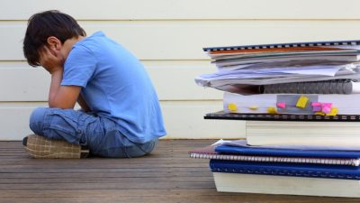Boy diagnosed with Dyslexia sitting with head in hands and stack of books near him outside