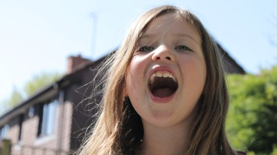 A young girl with nonverbal learning disorder, not ADHD, yelling in front of her house