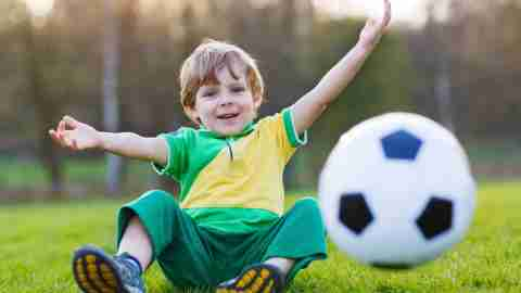 Preschool aged boy with ADHD sitting in field throwing soccer ball towards viewer