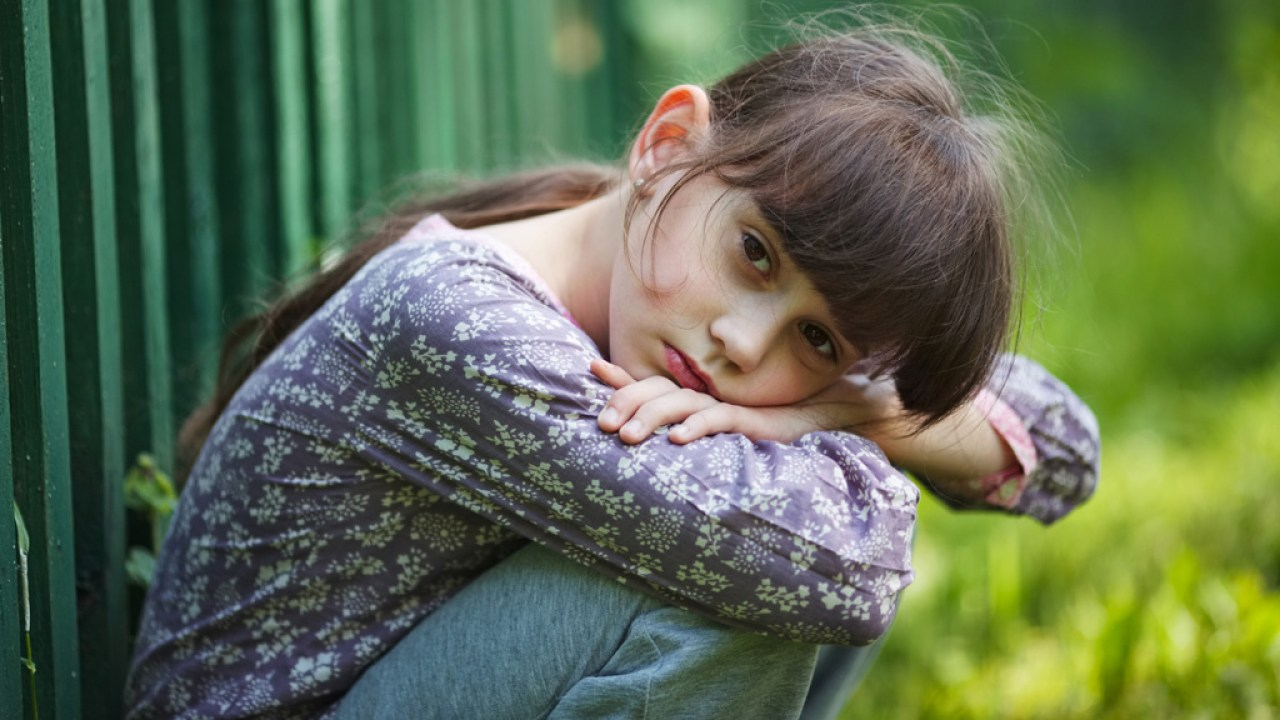 A young girl dealing with ADHD inattention, sitting with her head on her knees