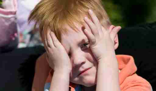 Close up of boy with ADHD covering face and unable to make eye contact