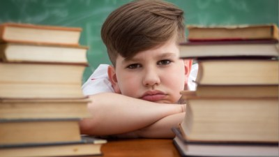 Boy with ADHD and a tic problem leaning on desk with books on it and chalkboard in background