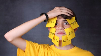 Boy with executive function disorder frustrated by tasks listed on post-its on his face
