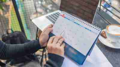 Mom with ADHD pointing at calendar with pen and laptop nearby