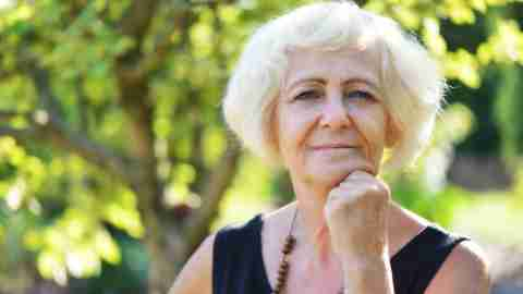 Older woman with ADHD staring into distance with fist under chin outside
