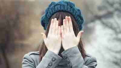 Girl with ADHD covers face with hands outside