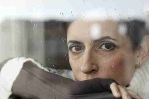 A woman with depression symptoms stares out a rainy window.