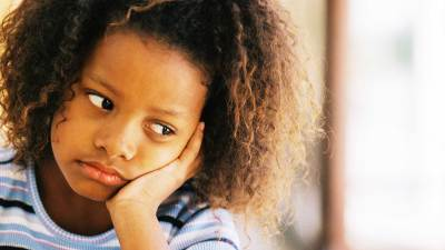 A sad girl with a hand on her face has Bipolar Disorder, which can occur in children with ADHD
