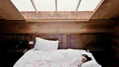 A woman sleeps well into the day after experiencing symptoms of insomnia the night before.