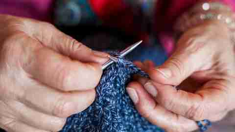 Close up of hand of elderly woman with ADHD knitting