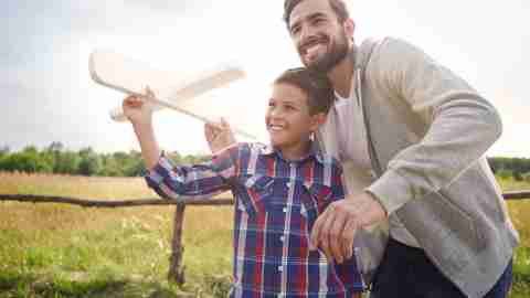 Father and son with ADHD fly paper airplane outside in field