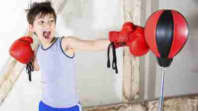 Boy with ADHD wearing boxing gloves and taking out aggression on punching bag