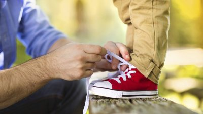Father teaching son with ADHD to tie shoe laces