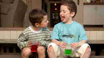 Two boys with ADHD sit on steps outside drinking colorful soda and sticking tongues out.