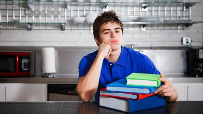 Teen boy with ADHD sitting at kitchen counter with stack of books in front of him staring into space