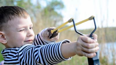 A happy child playing with a slingshot, having improved ADHD symptoms through parent-child interaction therapy