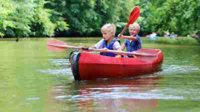 Two boys with ADHD kayaking on lake at summer camp