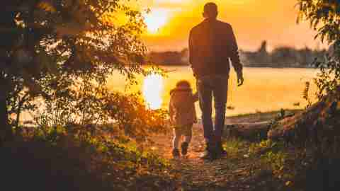 Single father walking with ADHD child toward lake at sunset