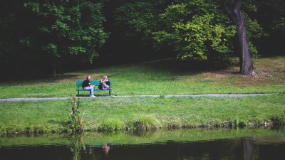 Father and daughter with ADHD talking on bench in park by lake