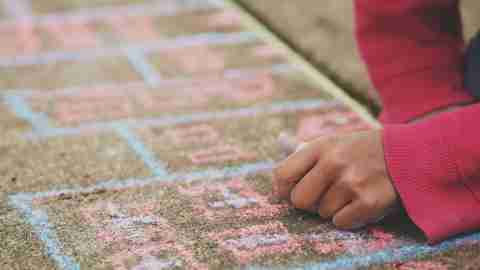 Kinesthetic learners benefit from hands-on experience, lik this child drawing on the sidewalk with chalk